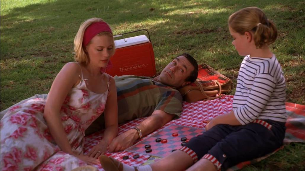 Don Draper having a picnic with his family. He's wearing a patterned sport shirt with a flared collar.