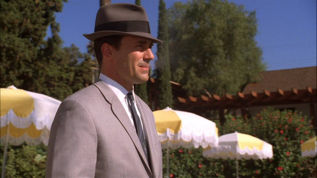 Don Draper standing by the pool side wearing a gray fedora hat with black band, gray suit, and white dress shirt.