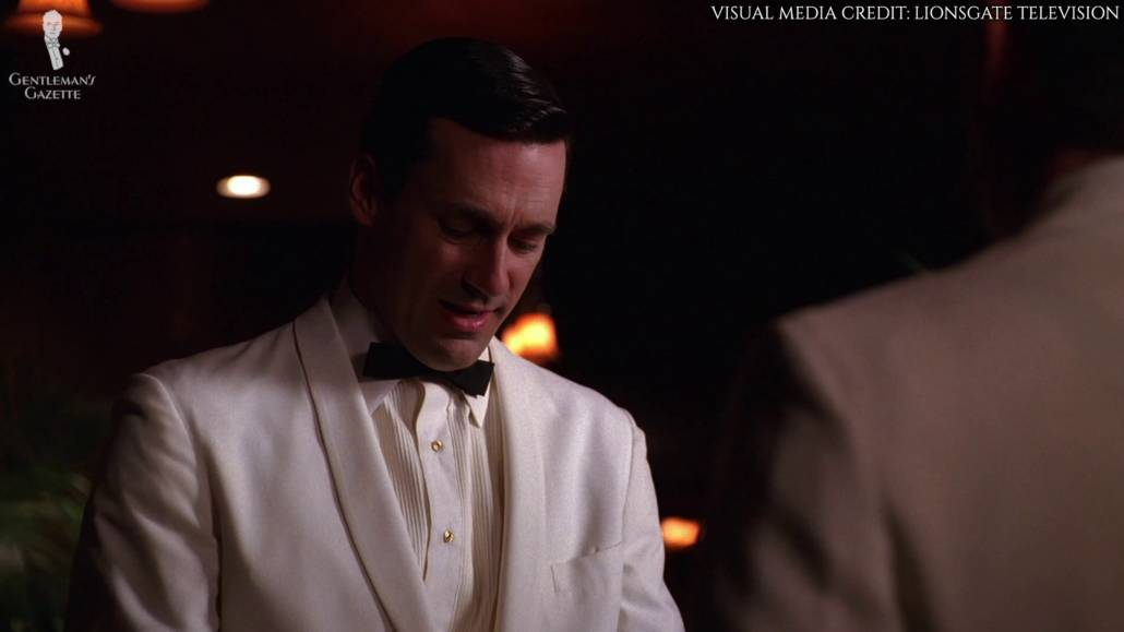 Don Draper donning a single button white dinner jacket with a very narrow shawl collar with a flat pocket.He's also wearing a white pleated shirt with gold shirt studs and a slim batwing bow tie.