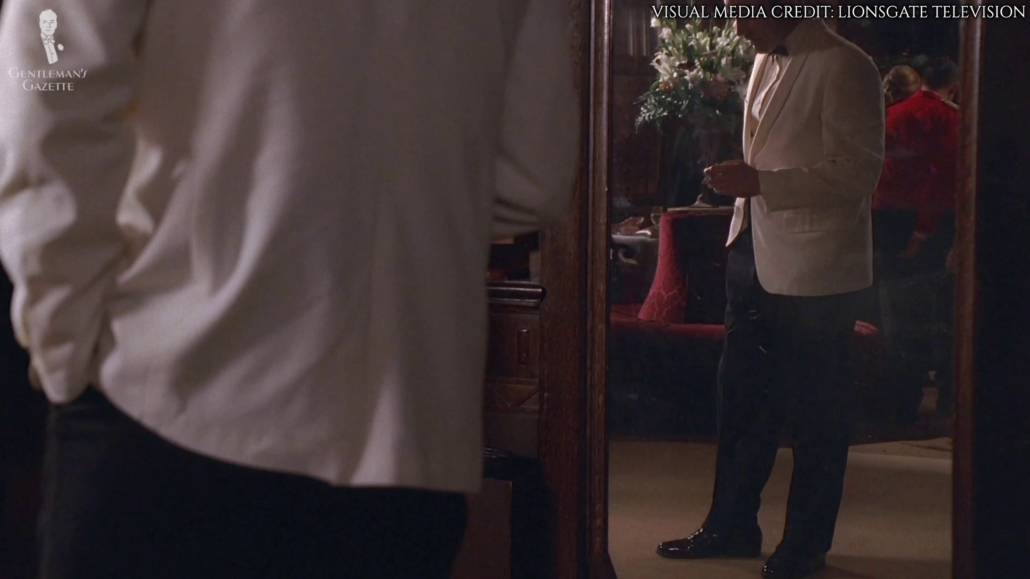 A reflection in the mirror showing Don Draper wearing a black trouser and a black shoes with his dinner jacket.