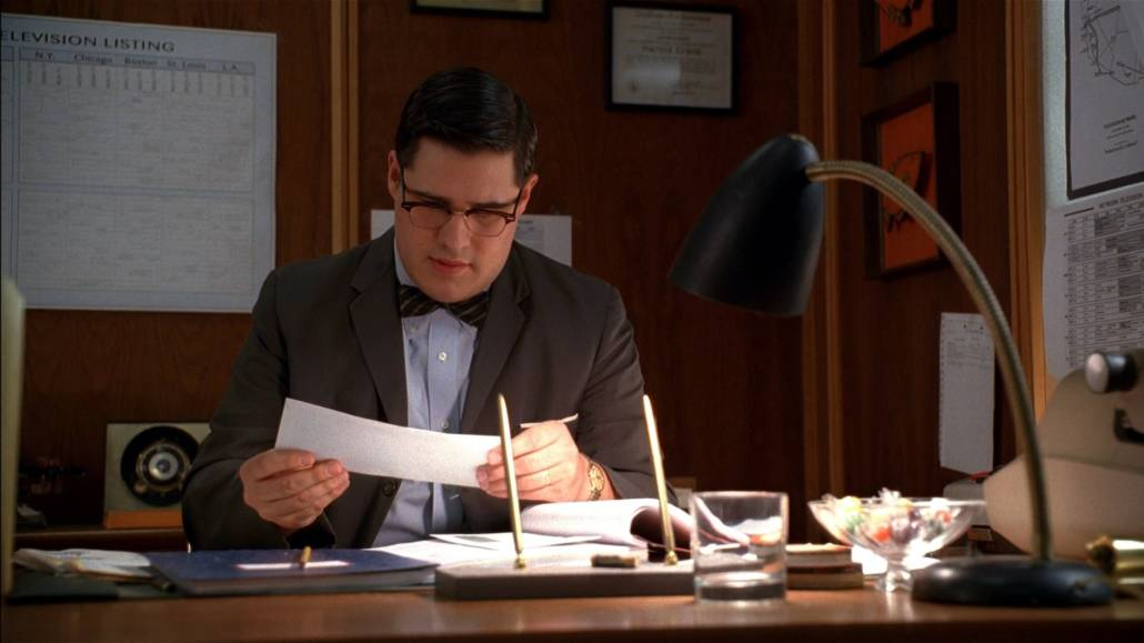 Harry Crane sitting at his desk and looking at a letter. He is wearing an unbuttoned suit jacket, a patterned bow tie, and a dress shirt