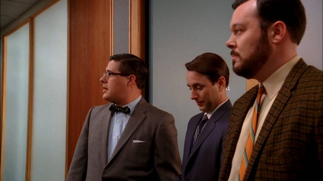 Harry Crane, Peter Campbell, and Paul Kinsey. Crane is wearing a mid-brown suit with a pale blue dress shirt and a patterned bow tie, Campbell is wearing a striped tie, white dress shirt and a somewhat navy blue suit, and Kinsey is wearing a checked sport coat with a pale yellow shirt and an orange striped tie.