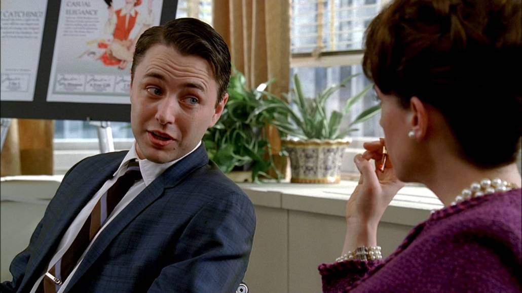Pete Campbell having a conversation with a colleague; he is wearing a lighter than navy suit and a striped tie.