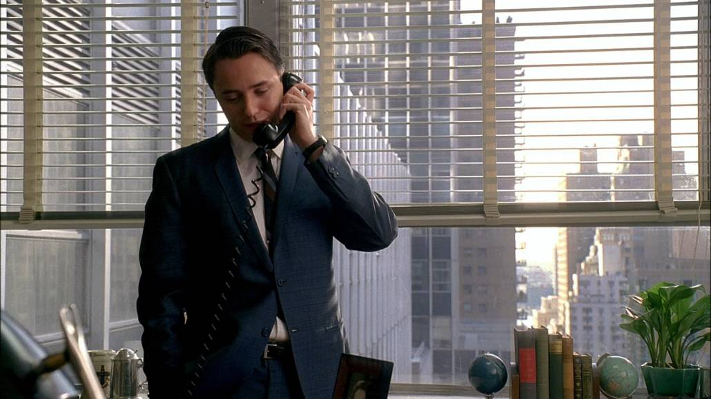Pete Pete Campbell in a lighter-than-navy blue suit with two buttons and skinny lapel with a somewhat elevated gorge. He is currently standing up and talking on the telephone.