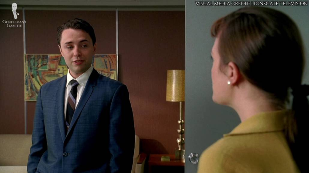 Pete Campbell wearing a mid-blue suit, white dress shirt with spread collars, and a striped tie.