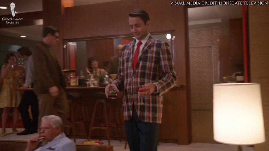 Pete Campbell walking across the room with drinks in both his hands. He's wearing a madras jacket, orange tie, and navy trousers.