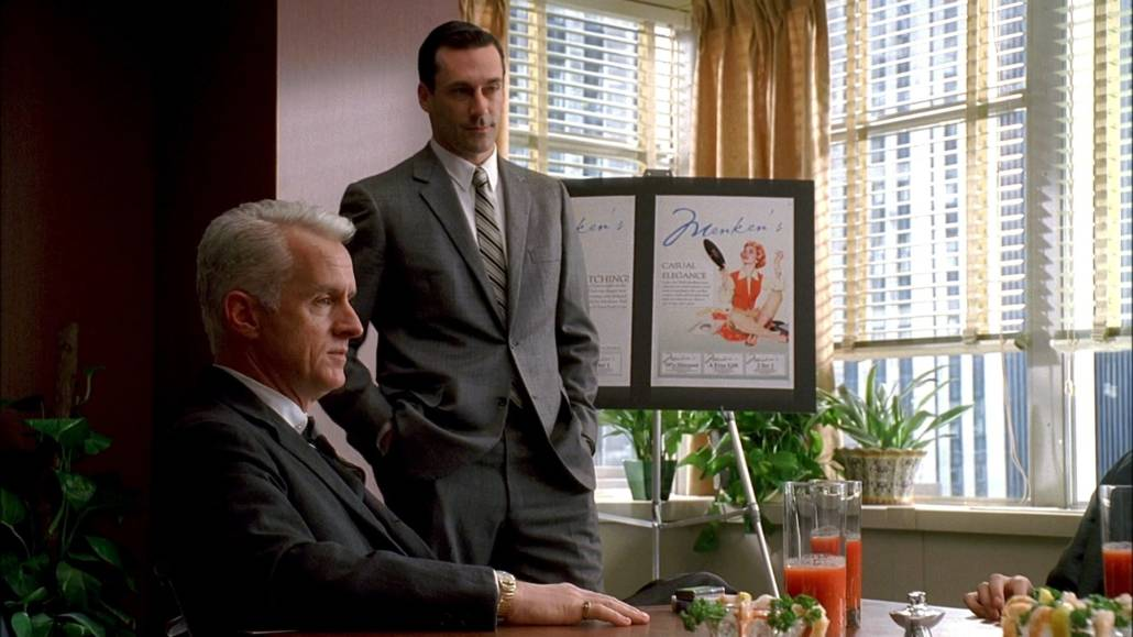 Don Draper standing beside a sitting Roger Sterling. Both are wearing business suits