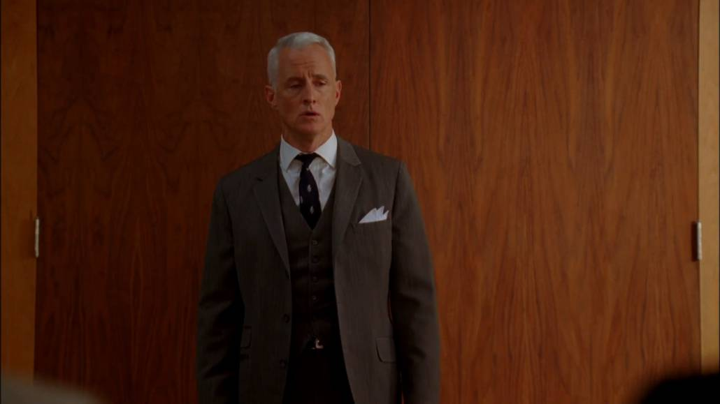 Roger Sterling wearing a three-piece charcoal suit, white pocket square, white dress shirt, and a navy tie.