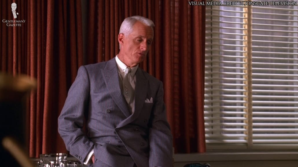 Roger Sterling wearing a slate blue, double-breasted suit with fine stripes in pale gray and orange with the bottom button undone.