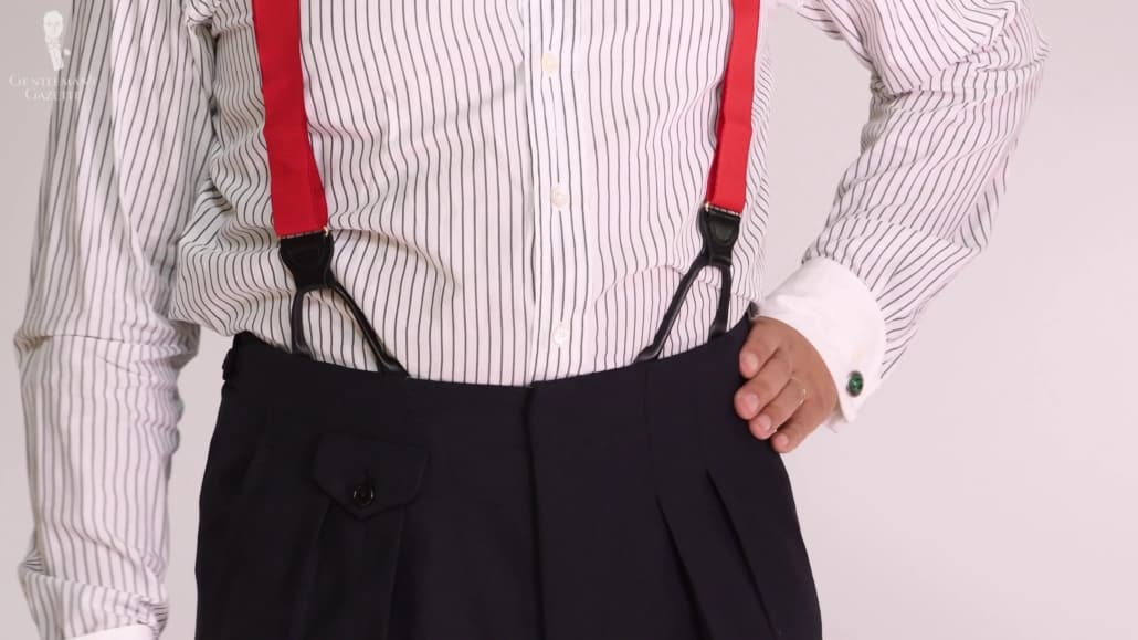 An image of Raphael focused on his red suspenders attached to his navy pleated trousers