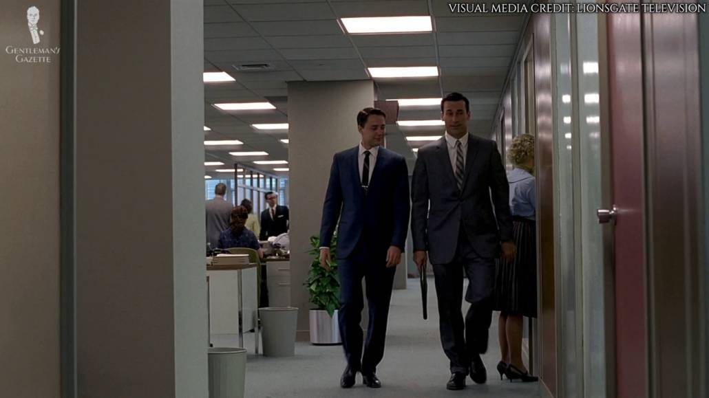 Don Draper and Peter Campbell walking along the hallways. Both are wearing business suits.