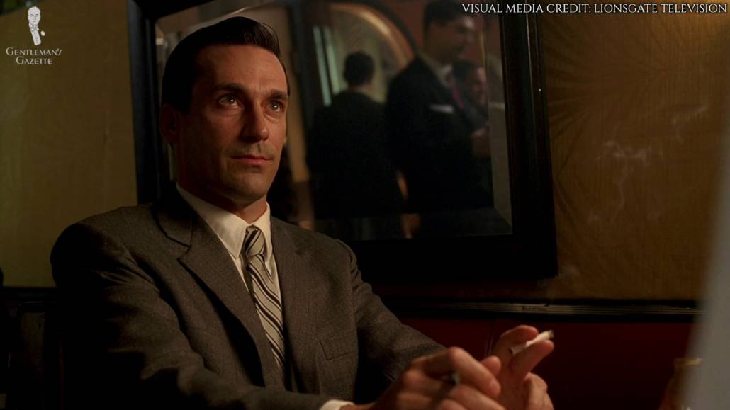 Don Draper in a classic business suit with notched lapel. He's currently sitting and staring at the person he was talking to who was not included in this frame.