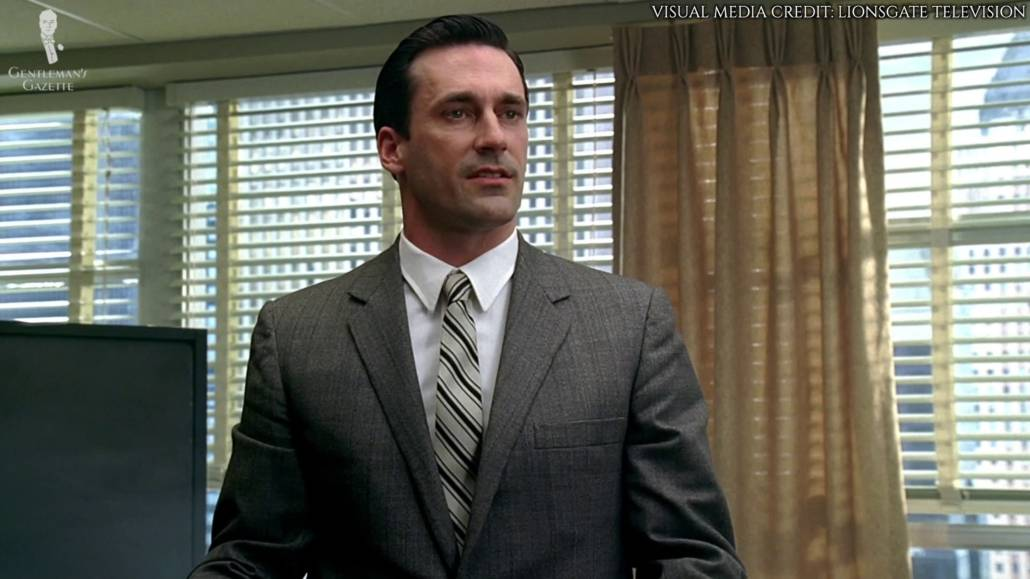 Don Draper in a light gray suit, white dress shirt with point collar, and stripe patterned tie.