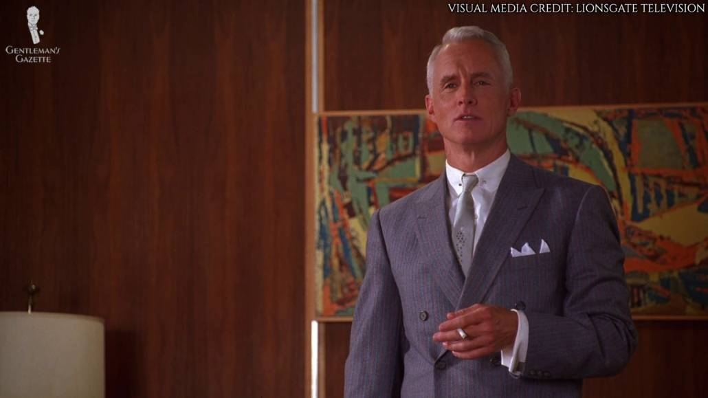 Roger Sterling wearing a slate blue, double-breasted suit with fine stripes in pale gray and orange, silver collar bars, silver, palish-blue tie with a fairy dust medallion detailing, white dress shirt with French cuffs, and silver cufflinks. He is also holding a cigarette in his left hand.