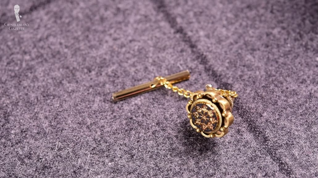 A gold tie tack attached on a t-bar