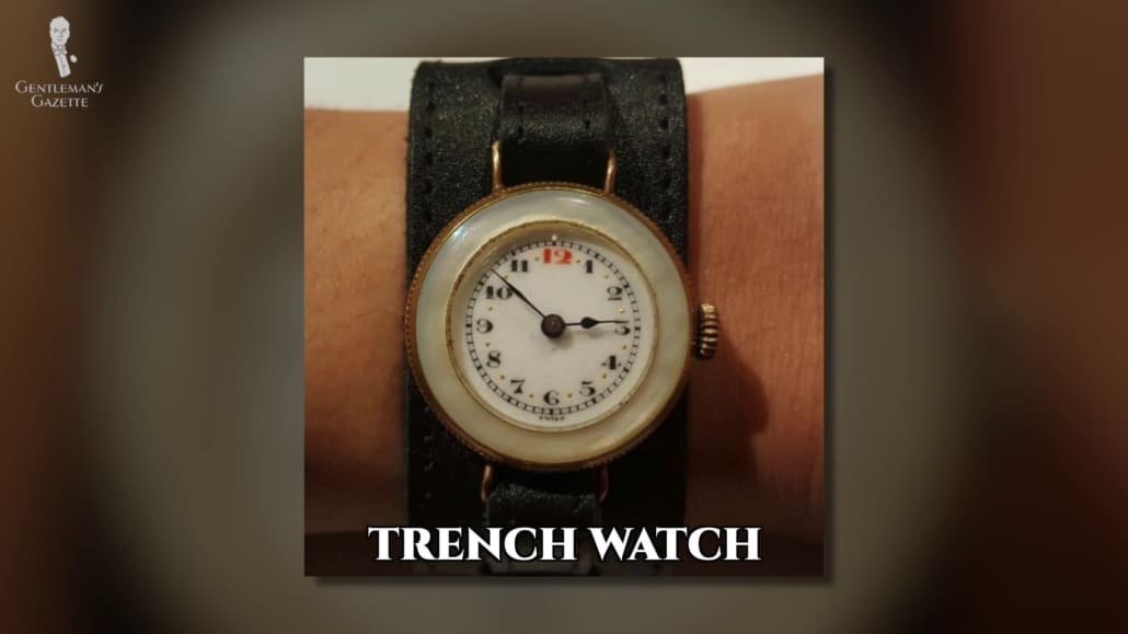 An old trench watch with a black leather strap.