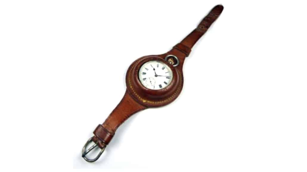A wristlet with a leather strap and a pocket watch inside it