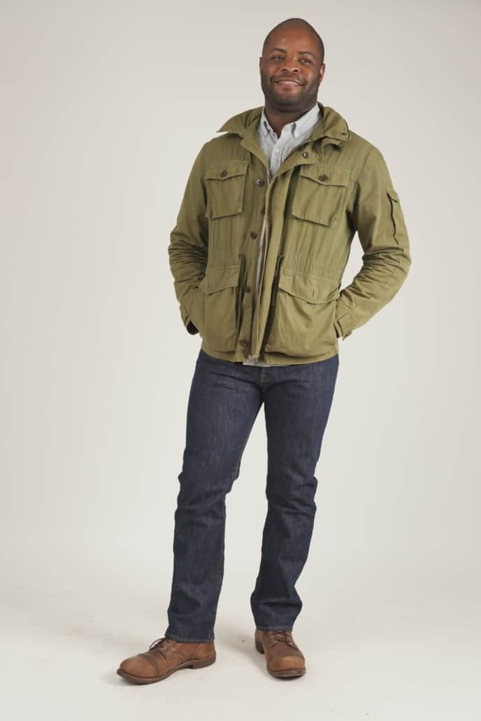 Smiling Kyle wearing a green jacket, dark wash Levi's 501 jeans, and brown Red Wing Boots