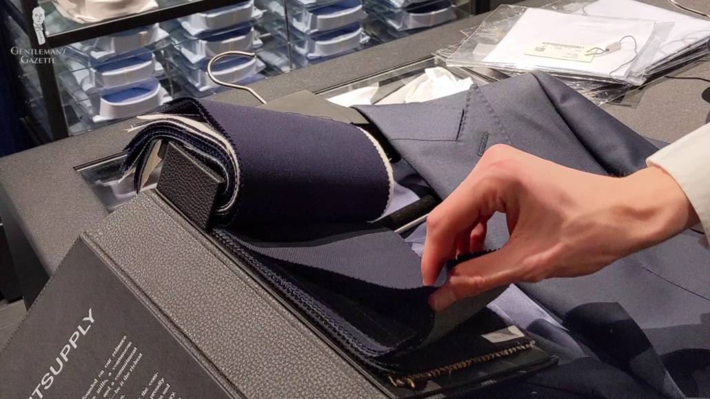 Preston checking the texture of suit fabric samples from SuitSupply.