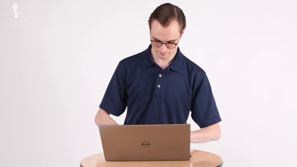 Preston standing while typing on a laptop; he's wearing a navy polo shirt