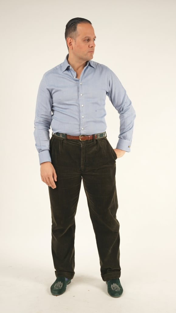 Raphael wearing his made-to-measure shirt from 100 hands in a bluish gray color, dark brown corduroy pants, brown belt, and green velvet Albert slippers with Fort Belvedere logo.