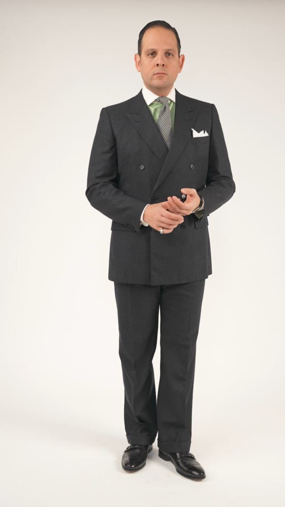Raphael wearing a double breasted suit, white pocket square, green dress shirt with a white Winchester club collar, and black monk strap shoes.