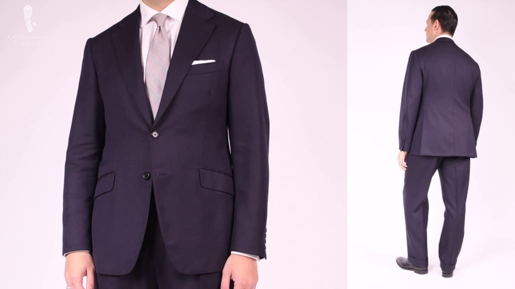 Raphael wearing a navy single-breasted suit, (front and back shot) silver tie, white pocket square in a tv fold, and black oxfords.