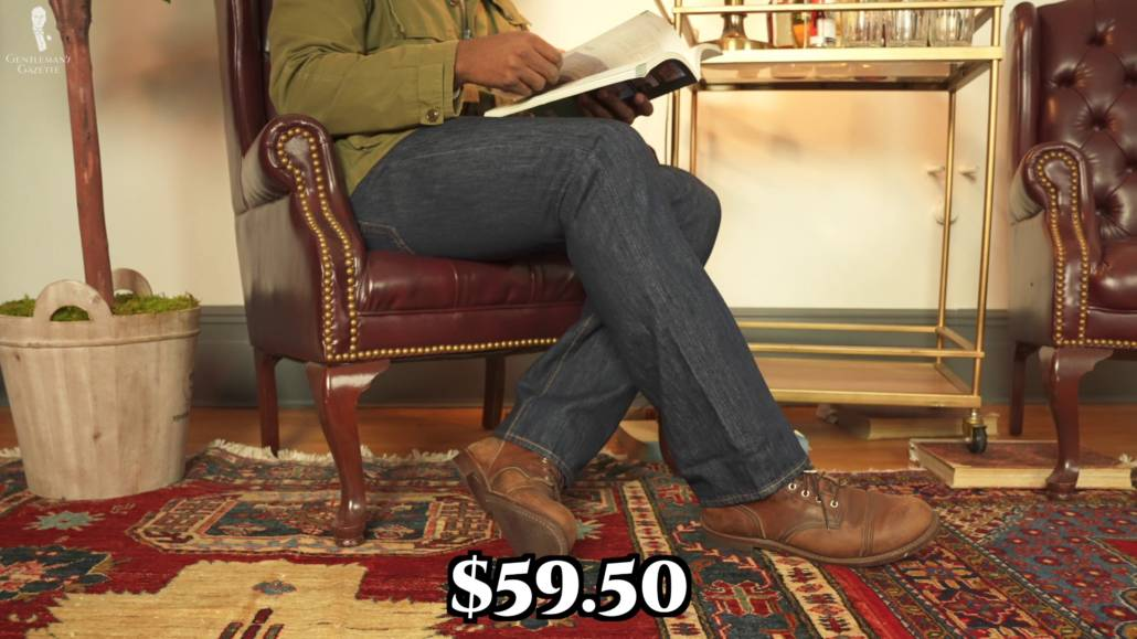 Image of Kyle's lower body showcasing the 501 jeans and his Red Wing Boots while reading a magazine. The price of the jeans is also captioned in the photo.