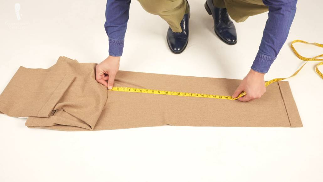 Raphael measuring the inseam of his pants while laid flat on the floor.