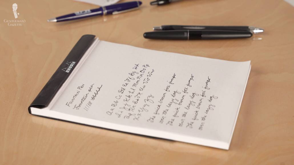 handwriting on a notepad with some fountain pens scattered on the side