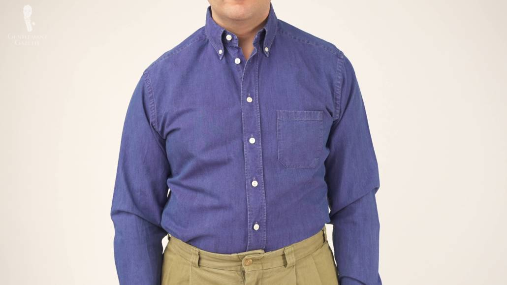 Raphael standing in a more relaxed manner; he's wearing a blue denim shirt and khaki chinos