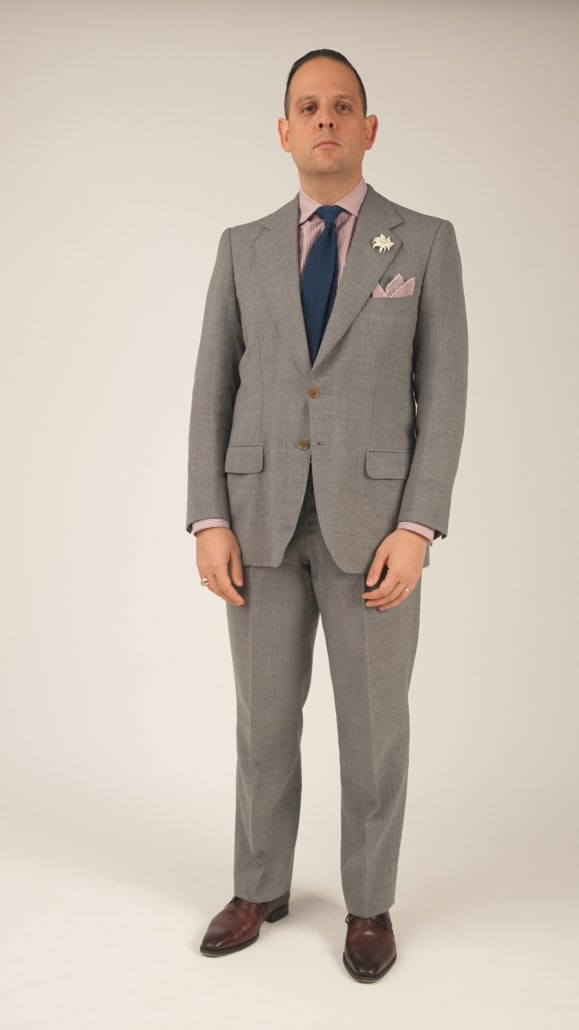 Raphael wearing a grey A Caraceni suit with red and white striped shirt, navy knit tie, white boutonniere and light red pockets square.
