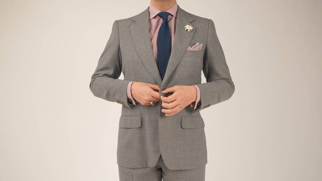 Raphael buttoning his suit jacket; he's wearing a gray suit with flap pockets, Light red striped dress shirt, navy tie, white boutonniere, and a light red pocket square from Fort Belvedere.