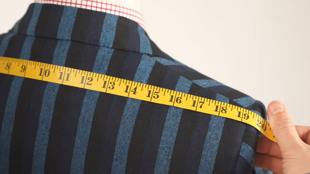 Shoulder measurement on a striped patterned suit jacket on a mannequin