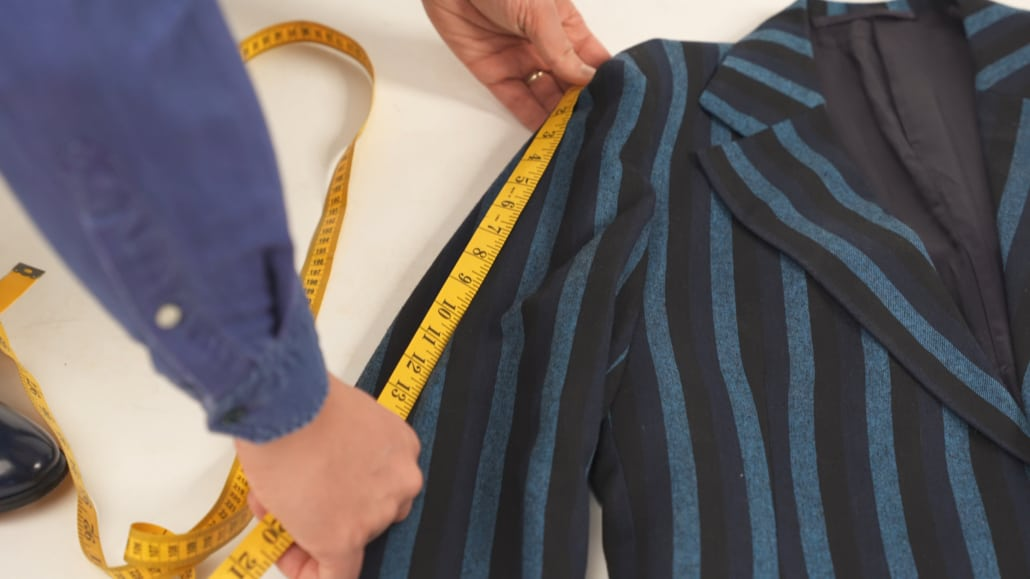 Raphael measuring a patterned suit jacket's sleeve length on the floor.